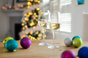 Glasses of wine on table with holiday decorations